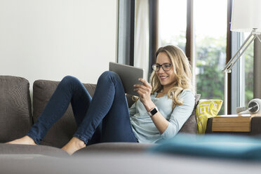 Smiling woman at home on couch using digital tablet - SBOF000096