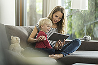Mother and son on couch with digital tablet - SBOF000102