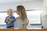 Mother holding son eating croissant - SBOF000105
