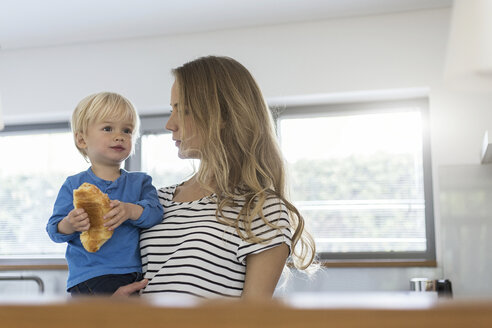 Mother holding son eating croissant - SBOF000105