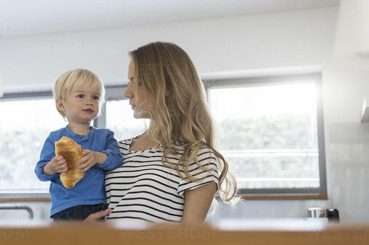 Mother holding son eating croissant - SBOF000105 - Steve Brookland/Westend61