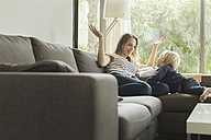 Mother and son at home playing on couch - SBOF000114