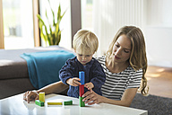 Mother and son stacking building bricks in living room - SBOF000117
