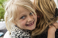 Portrait of happy blond girl hugging her mother - TCF004983