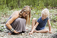 Mother and her little daughter looking for stones in nature - TCF004998
