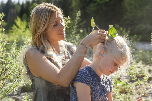 Mother pinning leaves in her daugther's hair - TCF005004 - Tom Chance/Westend61