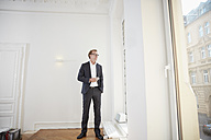 Businessman in the office looking through window - RHF001608