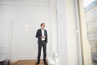 Businessman in the office looking through window - RHF001608