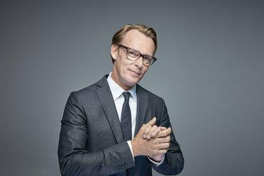 Portrait of smart businessman rubbing his hands - RHF001611