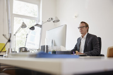 Businessman sitting at desk in an office working with computer - RHF001620