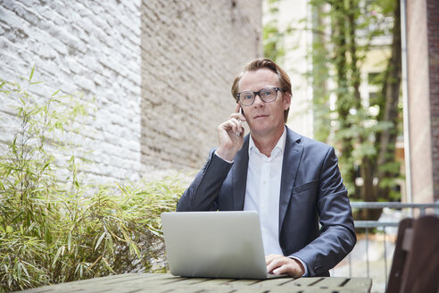 Telephoning businessman with laptop sitting at table in a backyard - RHF001629