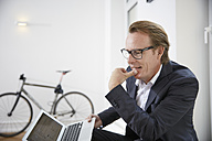 Pensive businessman with laptop - RHF001635