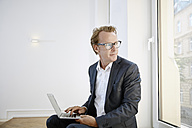 Businessman with laptop looking through window - RHF001638