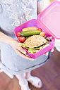 Girl holding lunch box with healthy food - MJF001849