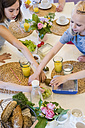 Girls reaching for food on laid table - MJF001864