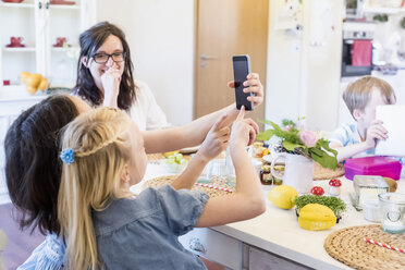 Two girls using smartphone at table - MJF001867