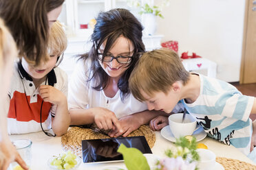 Mother and three children sharing digital tablet - MJF001870