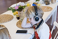 Boy with cell phone and headphones at table - MJF001885