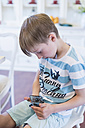 Boy sitting looking at cell phone - MJF001891