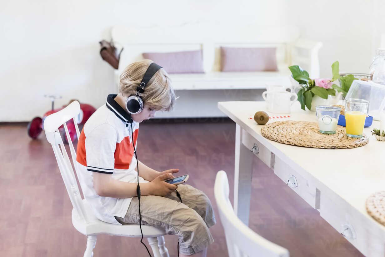 Boy wearing headphones looking at cell phone - MJF001897 - Jana Mänz/Westend61