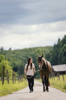 Young woman leading young brown horse on a field path - MIDF000728