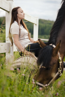 Young woman with brown horse having a break on paddock - MIDF000734