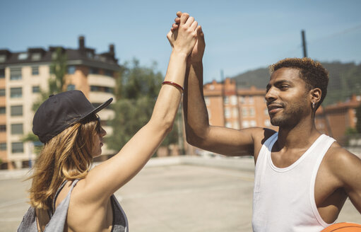 Young couple giving high five on basketball court - DAPF000165