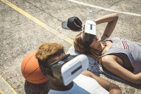 Young couple using virtual reality glasses, resting heads on basketball - DAPF000171