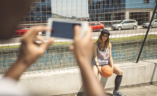 Young man taking photo of young woman at basketball court - DAPF000177