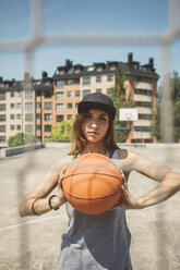 Young woman with cap holding basketball - DAPF000180