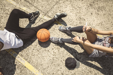 Young couple sitting on ground with basketball and smart phone - DAPF000186