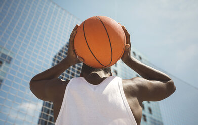 Young man holding basketball behind his head - DAPF000192