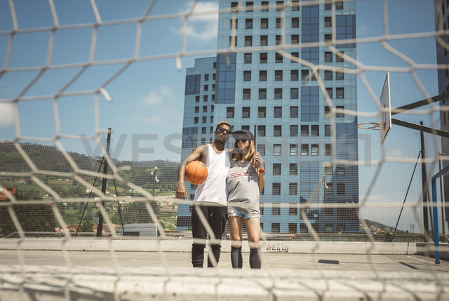 Young couple standing on basketball field, looking at camera - DAPF000195