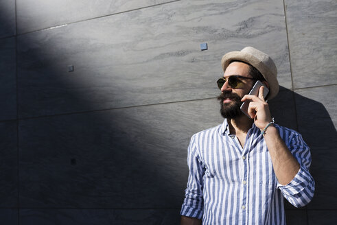 Bearded young man with sunglasses and hat telephoning with smartphone - FMOF000006