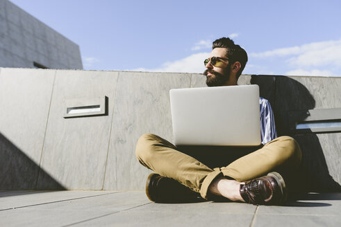 Young man sitting on the ground with laptop - FMOF000018
