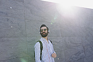 Bearded young man with sunglasses listening music with headphones - FMOF000021