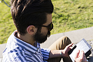 Young man using mini tablet - FMOF000024