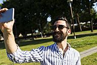 Smiling man taking selfie - FMOF000027