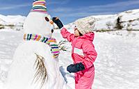 Spain, Asturias, Girl building a snowmen in winter - MGOF001971