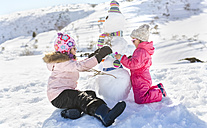 Spain, Asturias, kids playing with snowmen in a snowy mountains - MGOF001983