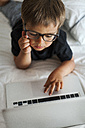 Little boy wearing glasses lying on bed using laptop - VABF000578