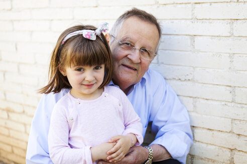 Portrait of grandfather with his little granddaughter in front of white brick wall - VABF000583