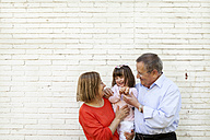 Grandparents with their granddaughter in front of white brick wall - VABF000586