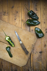 Sliced green pointed pepper and a pocket knife on wooden board - LVF004967