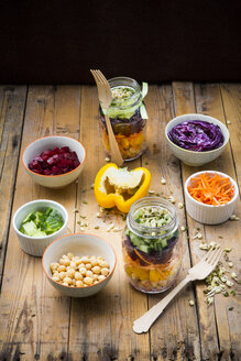 Two glasses of rainbow salad with chick-peas, sprouts and different vegetables and bowls with ingredients - LVF004973