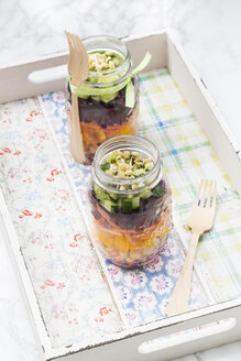 Two glasses of rainbow salad with chick-peas and different vegetables on wooden tray - LVF004976