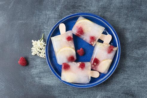 Homemade elderflower lemon raspberry ice lollies on plate - MYF001570