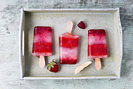 Homemade strawberry raspberry lemon ice lollies on tray - MYF001573