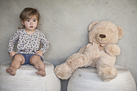 Serious baby girl and teddy bear sitting on stools - ZEF008727