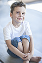 Portrait of smiling little boy sitting on floor - ZEF008730